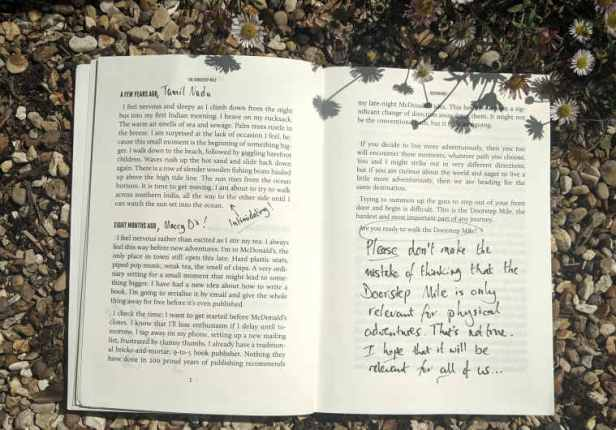 Open spread of paperback book The Doorstep Mile on gravel showing handwritten text on the print