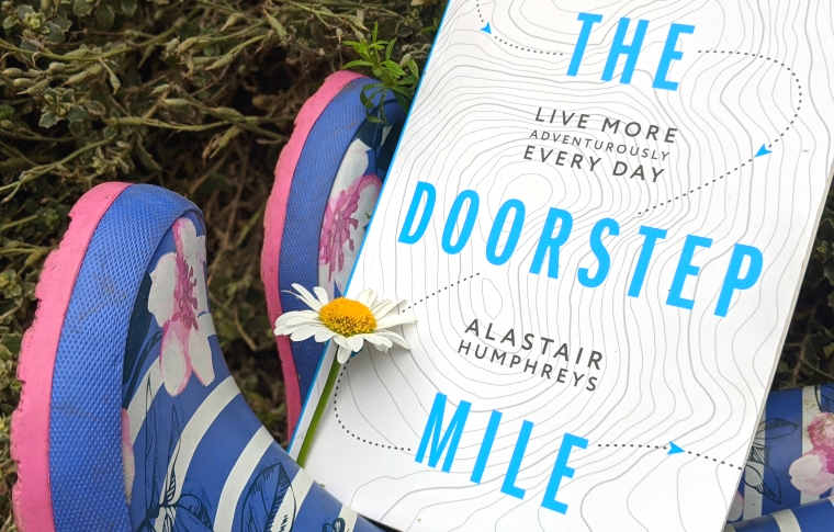 The Doorstep Mile book sitting on purple and pink wellington boots with daisy on cover