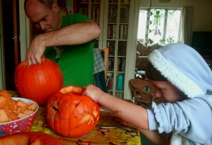 man-and-girl-carving-pumpkins-at-a-table-with-skeleton-in-background