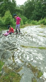 Children sitting on rock art, cup holes