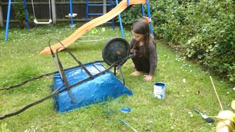 girl-painting-wheelbarrow-in-garden