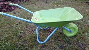 Child-size green and blue metal wheelbarrow on grass
