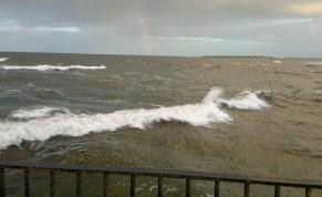 rough-grey-sea-with-small-island-and-faint-rainbow-at-horixon