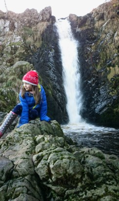 girl-in-blue-anorak-and-red-hat-hitting-on-rocks-with-waterfall-behind