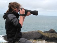 woman-on-rocks-overlooking-sea-taking-photo-with-large-zoom-lens-camera