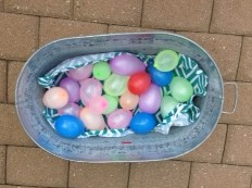 numbered water balloons in a bucket can be used in educational games