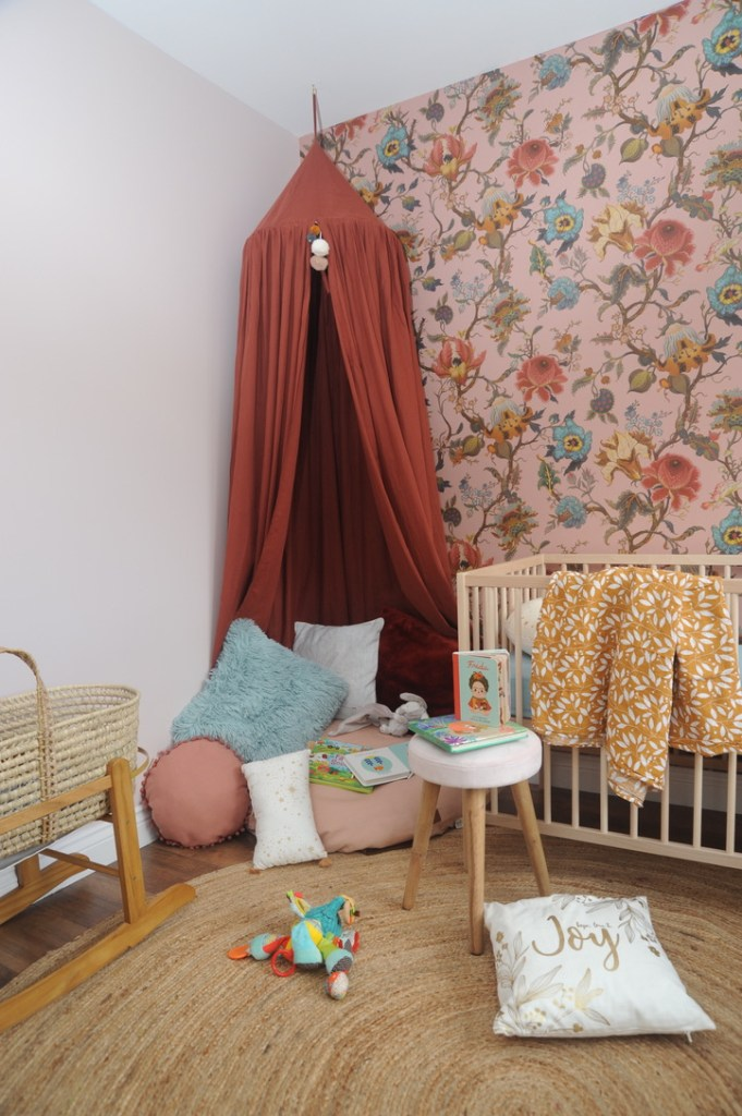 Corner of baby girl's nursery with canopied reading area floral wallpaper and wooden cot.