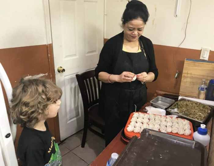Boy watches Nepali dumplings being made in Queens