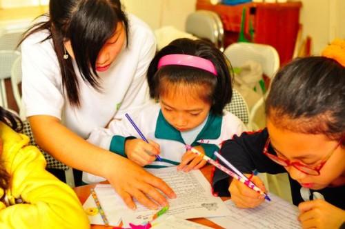 Bạn Hương SV trường ĐH Công đoàn giúp các em nhỏ điền mẫu đánh giá sau buổi đi bộ