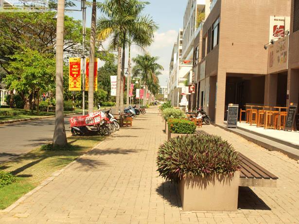 Một vỉa hè điển hình ở Phú Mỹ Hưng với gạch trồng cỏ ở dải đậu xe. Công trình trong Phú Mỹ Hưng hầu hết được thiết kế tiếp cận trực tiếp từ vỉa hè để định hình và tương tác với vỉa hè/không gian công cộng. Nguồn: tylevang
