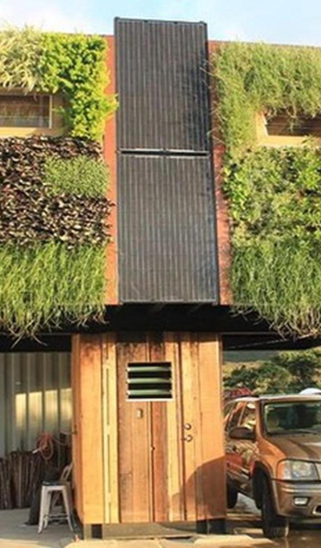 Nằm trên cột gỗ cao 2,4 - 3,6 m, ngôi nhà bảo phủ bởi cây xanh có nơi để xe bên dưới, đi kèm những tấm pin Mặt Trời và hệ thống dẫn nước mưa.