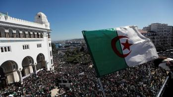 An Algerian flag flutters as people gather during a protest over President Abdelaziz Bouteflika's decision to postpone elections and extend his fourth term in office, in Algiers, Algeria March 15, 2019. REUTERS/Zohra Bensemra - RC13EC891FB0