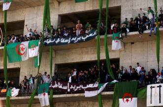 """Demonstrators carry their national flags as they stand atop of a building during a protest over President Abdelaziz Bouteflika's decision to postpone elections and extend his fourth term in office, in Algiers, Algeria March 15, 2019. The Arabic banners read: """"The People Want to Bring Down the Regime"""". REUTERS/Zohra Bensemra - RC1FF4A60230"""