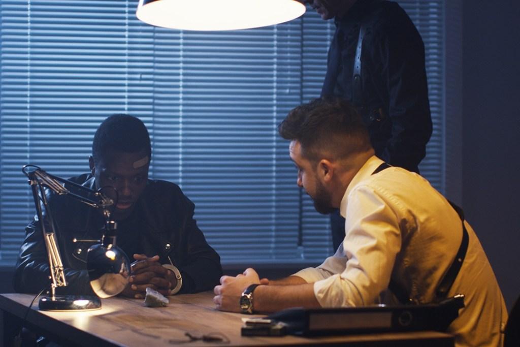 Medium shot of two policemen interrogating a drug dealer