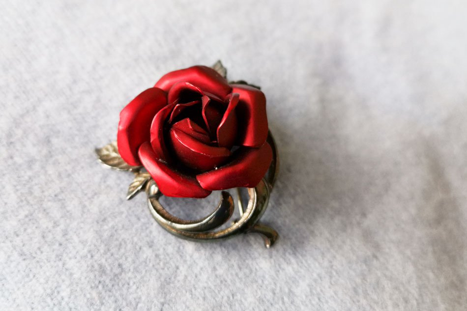 Vintage brooch for those romantic at heart. The single red rose brooch features a deep red wine colourse metal rose with a gunmetal colored leaves and vine. I remember my nan having one of these and the metal petals are so delicate that they really do resemble a rose. It is in good vintage condition with just very little wear to the edge of some petals which are not noticable when worn. The brooch has a strong rollover clasp. A perfect gift for your loved one on valentines day! Measurements 4 x 4 cm. Weighs 11 g. Presented in a satin drawstring bag.