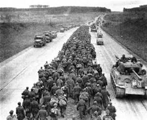 German prisoners of war shuffle down the median as US army vehicles race down the autobahn