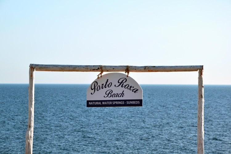 Undici spiagge imperdibili sull'isola di Zacinto: cartello di benvenuto a porto roxa, con il mare dietro