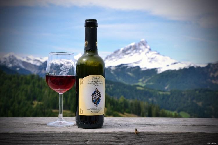 lista di rifugi in Alta Badia:bottiglia di santa magdalena con calice e vista sul sas de putia innevato al ranch da andrè