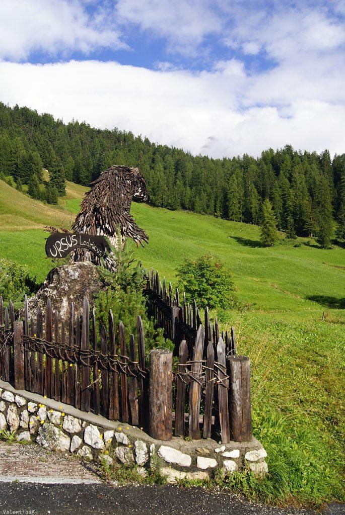 orso ladino in legno tra i prati
