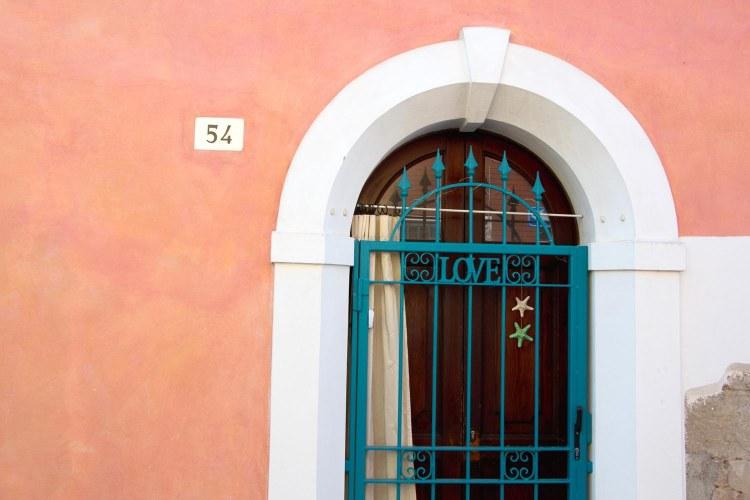 borgo san giuliano: una porta su un muro dipinto di rosa