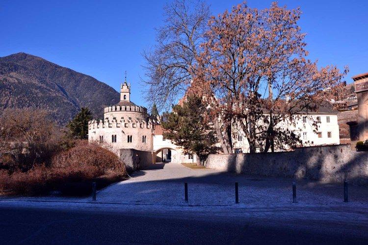 ingresso all'abbazia di novacella, con alberi e castello dell'angelo