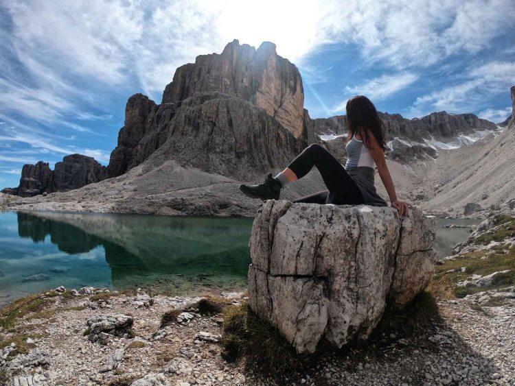 valentina in posa su roccia accanto al lago e alla cima pisciadù