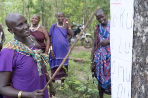 masai woman learning syllables with poster on tree