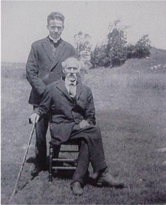 two men, unidentified outdoors, one sitting