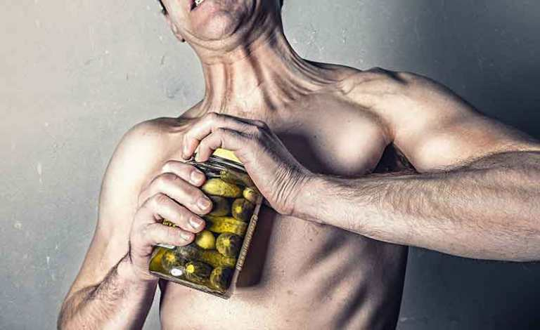 Man trying to open a jar of pickled cucumbers