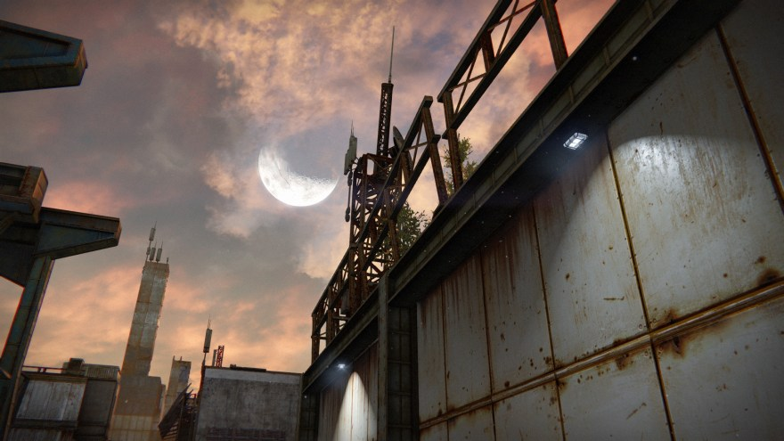 a bright dusk moon behind industrial structures