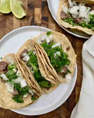 carne asada tacos with lime wedges