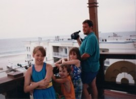 three small children and their father on a platform with the beach in the background