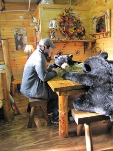 A young man sitting at a table with a stuffed bear