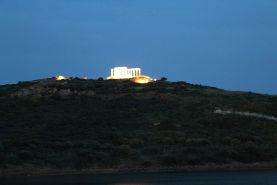 A stone temple lit up on the top of a mountain