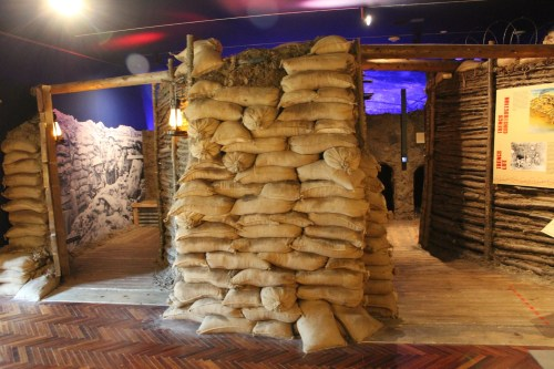 a small room with two doors. Sandbags are piled ot the ceiling, supporting the dirt and split log walls