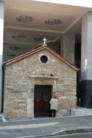 A stone church sits in the entryway to a modern building