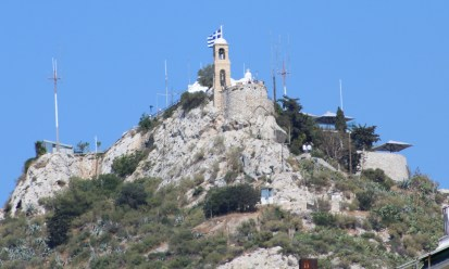 Greek Church flying the Greek flag on top of a stony hill
