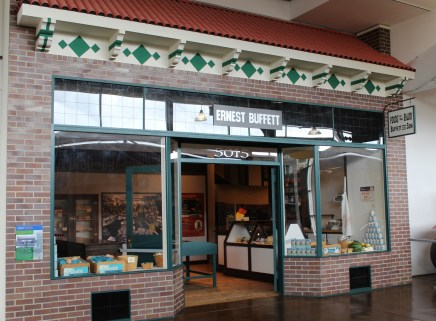 "a brick storefront with large display windows - a sign says ""Ernest Buffett"" above the double doors"