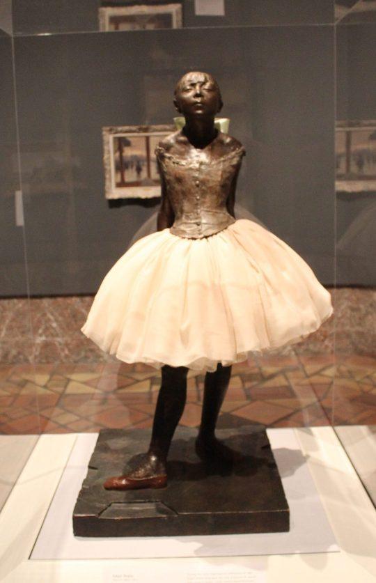 a bronze stature of a girl in a tutu