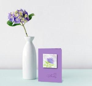 greeting card and purple hydrangea on aqua table display