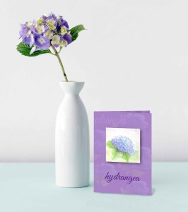 Hand Painted Watercolor Hydrangea on purple card displayed on aqua table with hydrangea flower in white vase category image