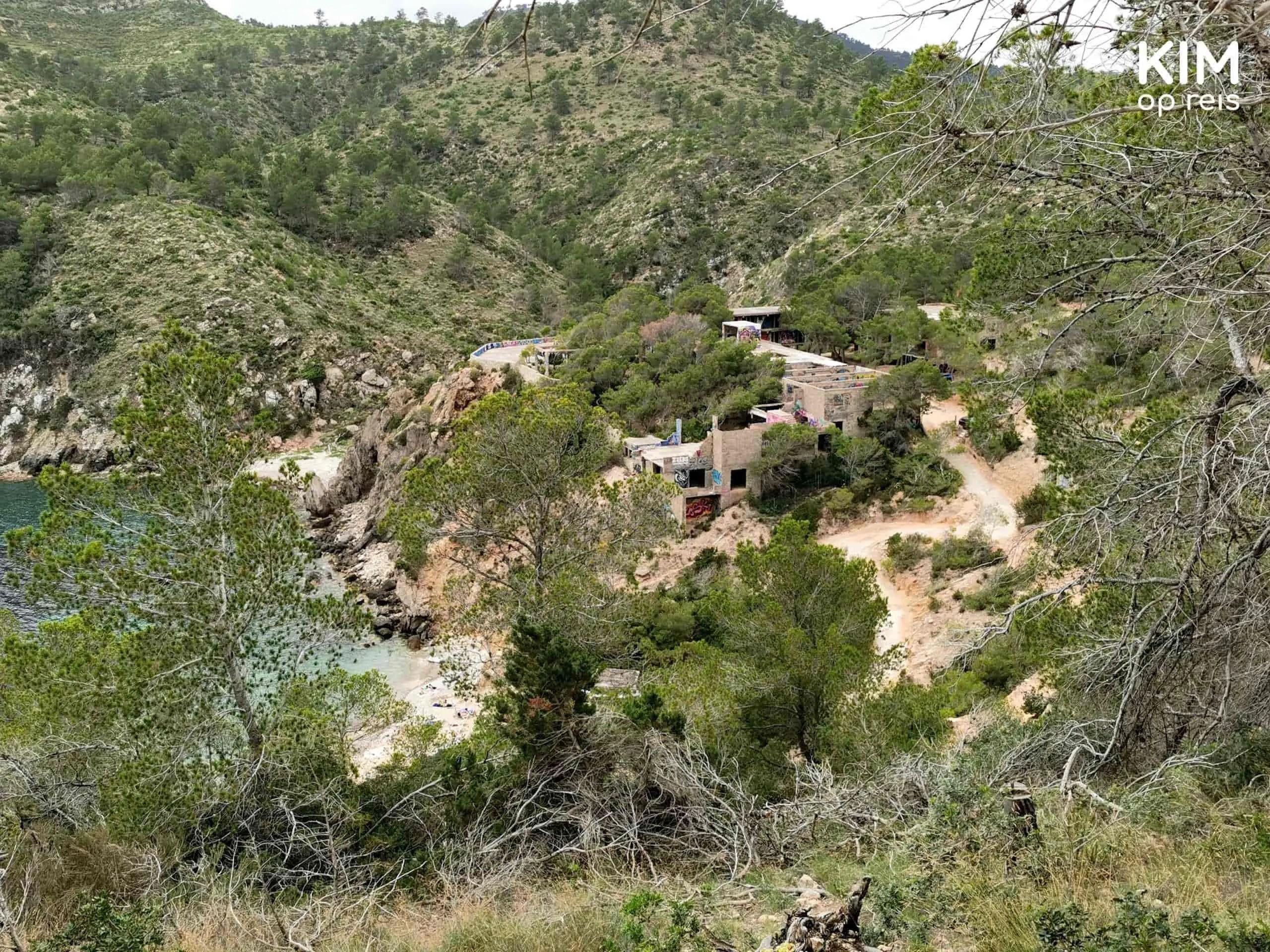 Cala d'en Serra baai: baai van bovenaf gezien, tussen de bomen door
