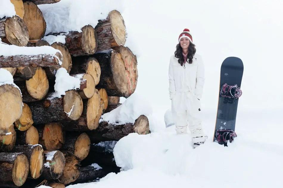 Duurzame skikleding: meisje staat in witte skikleding naast besneeuwde, afgezaagde boomstammen
