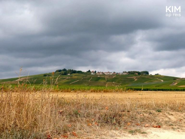 roadtrip champagnestreek: dorpje op een heuvel bij onheilspellende lucht