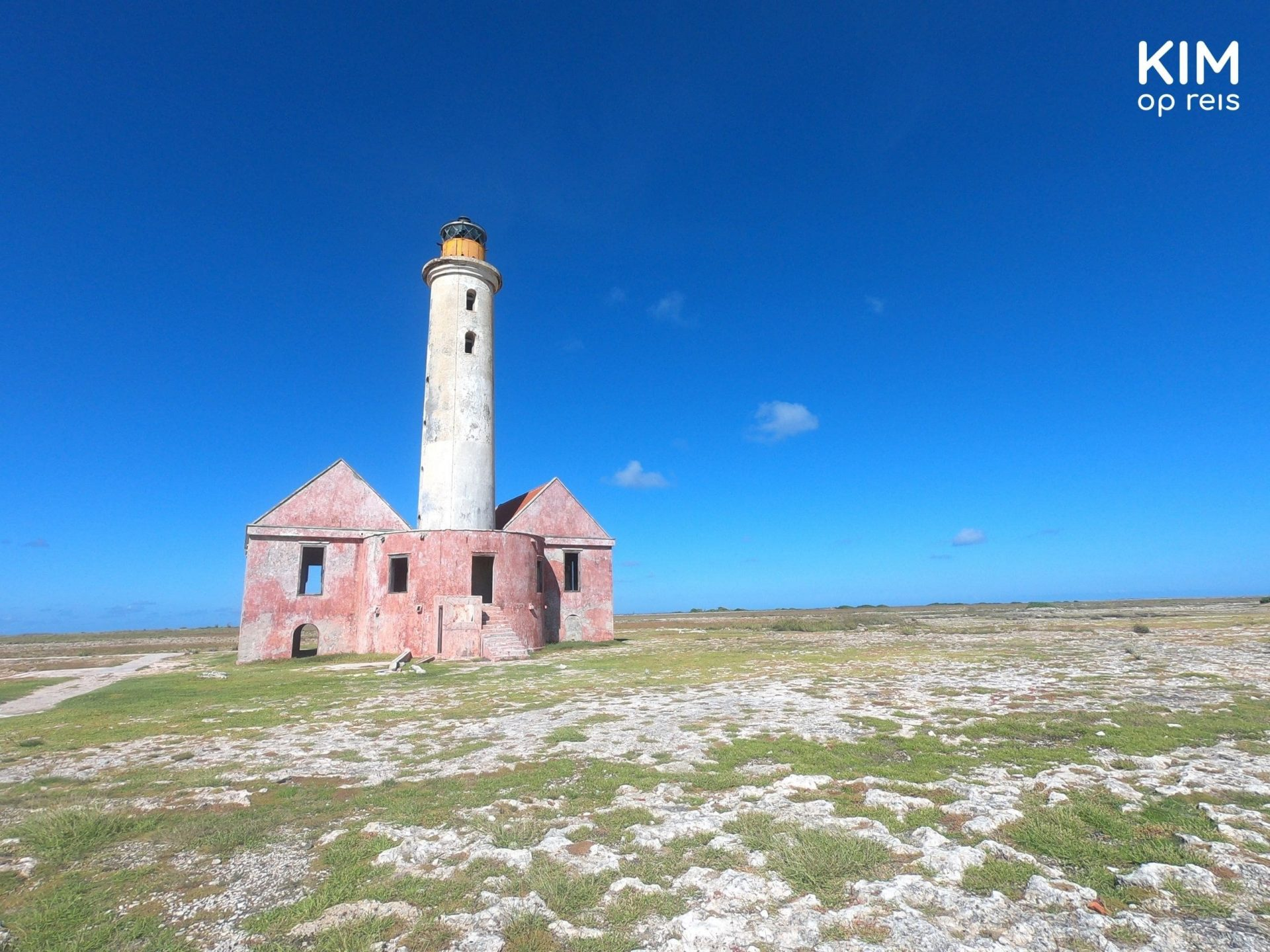 Prins Hendrik lighthouse Klein Curaçao: small, simple lighthouse with a white tower and a pink building on both sides