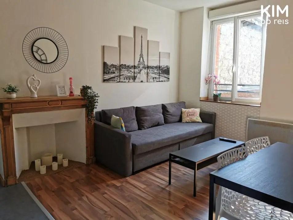 Airbnb Reims overnachten: woonkamer met een bank, een schildering van Parijs en een open haard met kaarsen