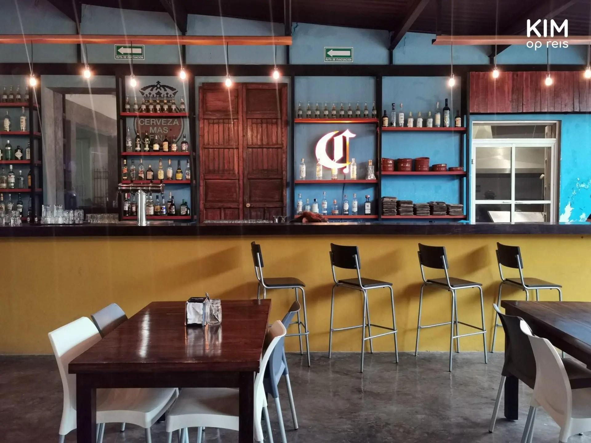 Bar Tobala 58: de bar, geverfd met blauw en geel en twee tafels ervoor