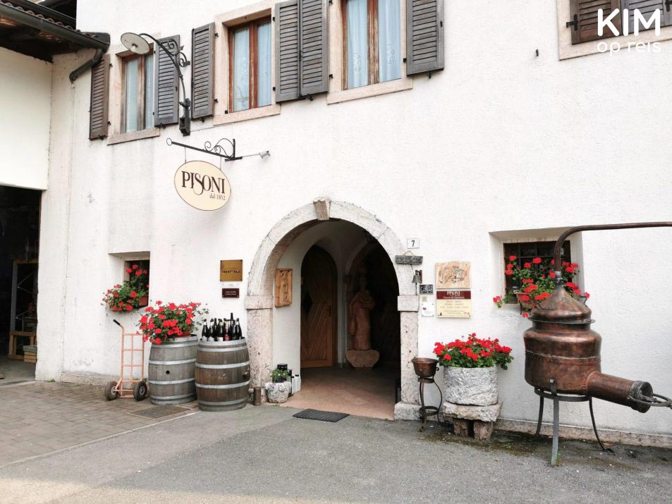 Cantina Pisoni - white building with shutters, a sign, red flowers, and wine