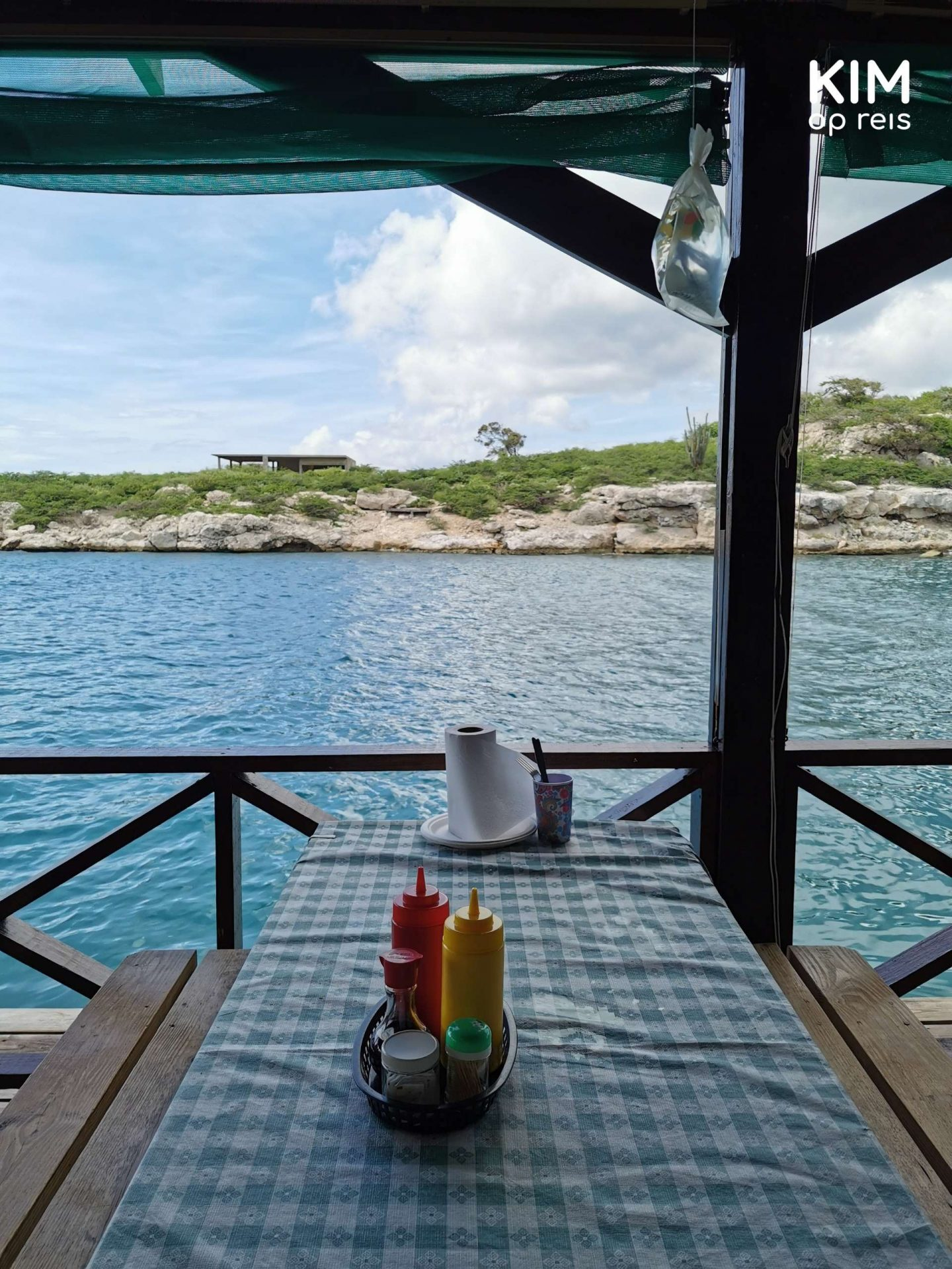 De Visserij view Curaçao: picnic bench right on the water, sauces on the table
