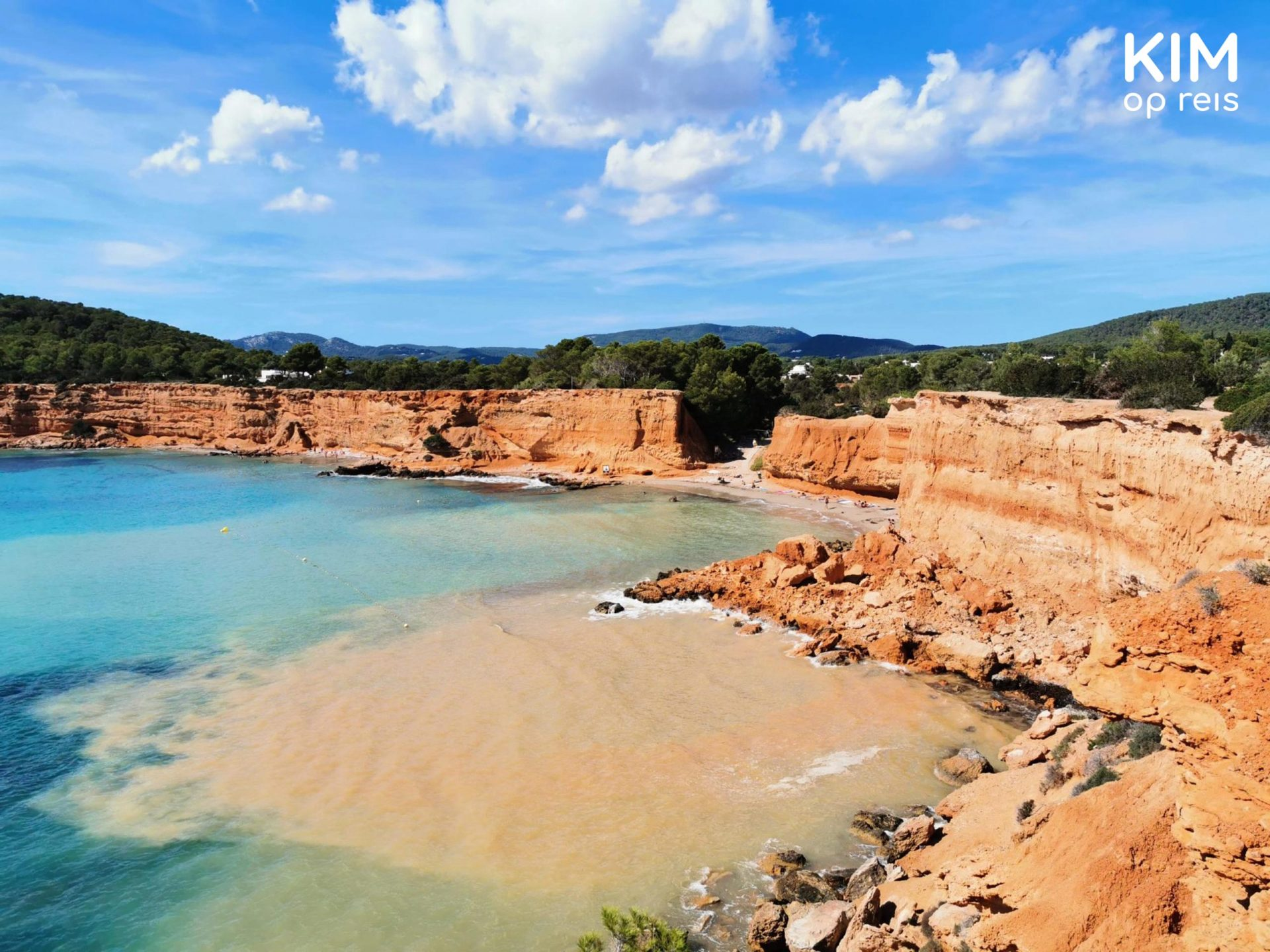 Es Bol Nou bay - terracotta colored cliffs with clear blue skies and azure blue ocean.